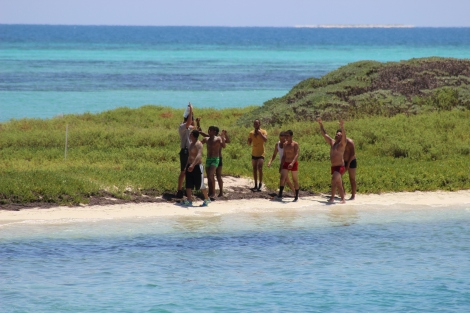 Exhausted, the Cuban immigrants walk along the Bush Key beach, to be greeted by a Dry Tortugas National Park ranger. Photo Source: Matthew Toro. August 4, 2015.